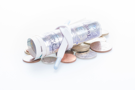 shoestring: Shoestring budget with British Pound banknotes and coins Stock Photo