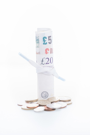 pennypinching: Shoestring budget concept with British Pound banknotes and coins Stock Photo
