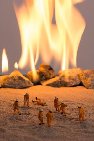fireman helmet: Miniature firemen at work near a real fire Stock Photo