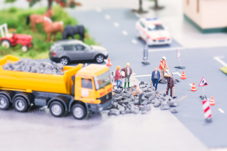 Road works with miniature workers in a country setting Stock Photo