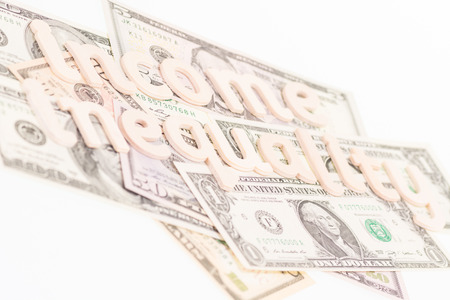 underpaid: Income inequality wooden letters on US banknotes Stock Photo