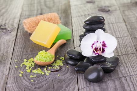 Spa with bath salt, soaps, loofah and black stones close up