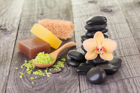 Spa with bath salt, black stones, soaps and loofah on weathered wood