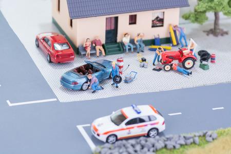 Miniature mechanics repairing a car and a tractor