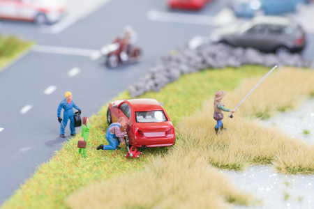 Miniature mechanic replacing a punctured tyre off the roadway