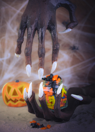 Pinhole effect Halloween witch hand, candy and pumpkin ornament Stock Photo
