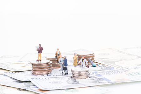 Miniature people on coins and banknotes Stock Photo