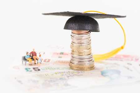 Miniature parents saving for their childs education fund Stock Photo