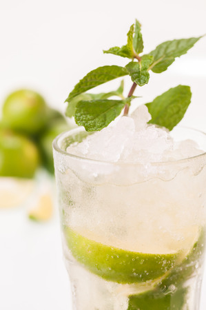 Mojito cocktail with lime fruits at the background
