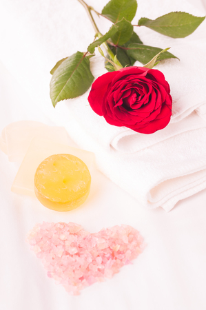 Romantic spa getaway with heart shaped bath salt and rose on bed Фото со стока