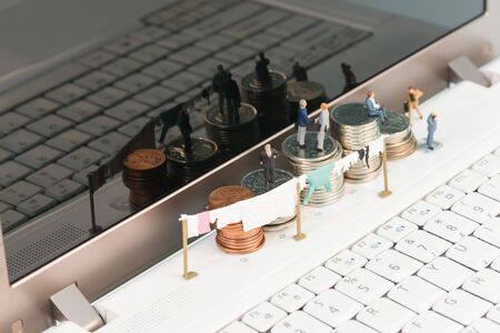 Money laundering with miniature people and. coins top view Stock Photo
