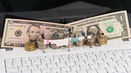 Money laundering concept with miniature people and coins