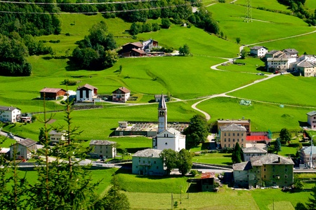 narrow gauge railways: View from Bernina Express, Alpine village with a church in the middle surrounded by green grass meadows