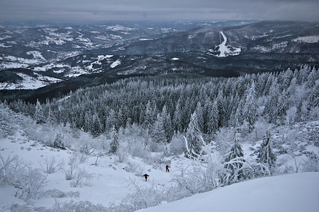 Lonely hikers wade through deep snow in mountain during winter  Babia Gora, Poland photo