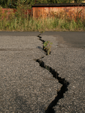 Cracked road damaged by earth movement photo