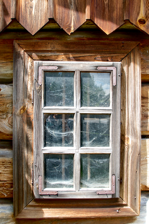 man made structure: Wooden window with cobwebs behind glass and arrow shaped roof hanging from top  Traditional cottage, Poland