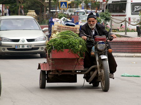 grocer: Old meets new on the streets of Turkish city. Grocer transporting his vegetables to bazaar market. Turkey, Middle East.
