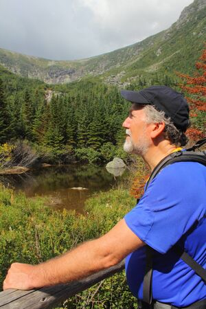 boreal: Senior backpacker at Hermit Lake with the headwall of Tuckermans Ravine in the distance. These are the slopes of Mt. Washington in the White Mountains of New Hampshire. The pond is still in the boreal forest zone on the mountain while the headwall is an