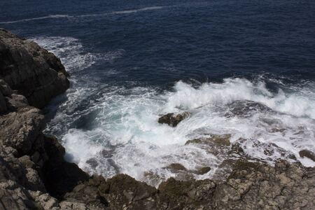 swirling: Waves swirling on the rocks off the shore of the Cape of Sorrento along the Amalfi Coast of Italy. These are tuff rocks of explosive volcanic origin. The waters are of the Mediterranean Sea. Stock Photo