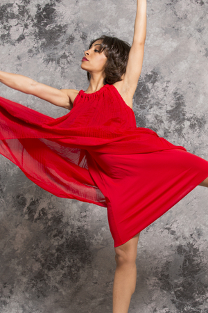 mottled background: AfricanAmerican female dancer in a red dress on releve in a studio session with a grey mottled background. Vertical image.
