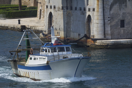 taranto: Commercial fishing boat heading in to the docks in Taranto Puglia Italy The Castle of Aragon is in the background with arches and stone construction dating to the 15th century. Stock Photo