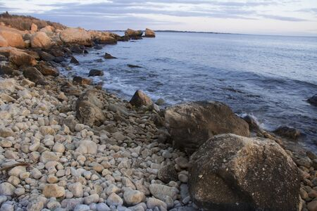 Curving shoreline with boulders and gravel on Long Island Sound of the Atlantic Ocean in Connecticut near sunset. Foto de archivo