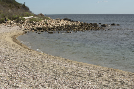 curving: Curving shoreline with boulders and gravel on Long Island Sound of the Atlantic Ocean in Connecticut near sunset. Stock Photo