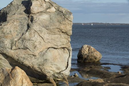 Giant rock on the beach with sailboats and waters of Long Island Sound of the Atlantic Ocean Connecticut.