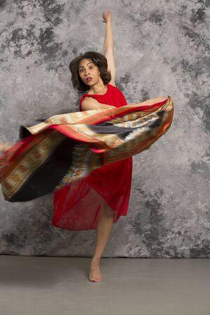 灰色背景: 灰色の背景に対してアフリカの布を渦巻く赤いドレスの女性ダンサー。垂直方向の画像。