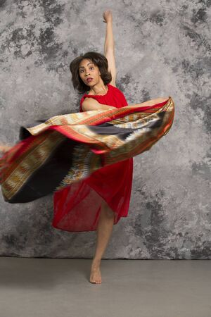 african fabric: Female dancer in red dress swirling African fabric against a grey background. Vertical image.