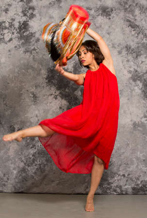 african fabric: Female dancer in red dress, holding African fabric in the air, with right leg kick against a grey background. Vertical image.