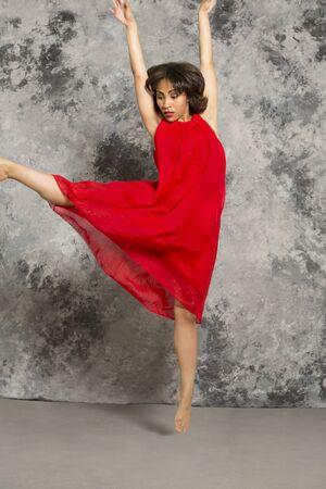 灰色背景: 赤いドレスの女性ダンサーは、右足のキックは、灰色の背景に対してジャンプします。垂直方向の画像。 写真素材