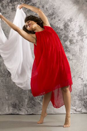 turns: Attractive young female dancer, representing diversity in dance, in red dress, in dramatic turns displaying white fabric against a grey background. Vertical image. Stock Photo
