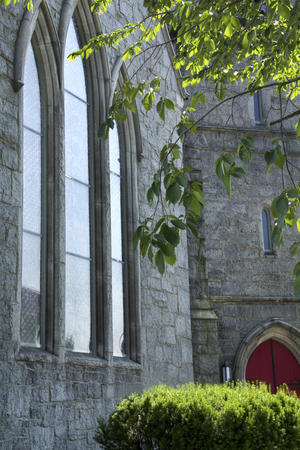episcopal: Narrow, pointed, vertical windows in gray stone wall, with green shrub and tree, outside St. James Episcopal Church, Keene, New Hampshire.