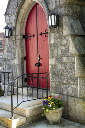 episcopal: Red, double doors of arched entrance to St. James Episcopal Church, with flowers in pot, from side view, downtown Keene, New Hampshire. Stock Photo