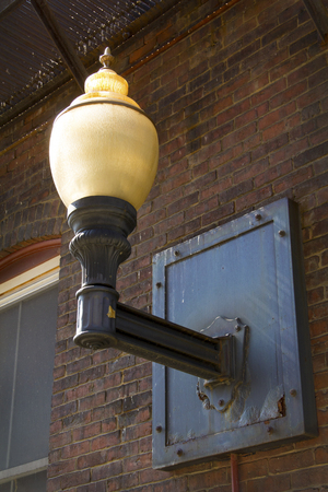 opalescent: Vintage light fixture, with yellowing glass globe and right angle iron support, on brick wall in alley, downtown Keene, New Hampshire.