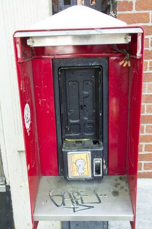 relict: Legacy phone booth kiosk, red, with phone missing, graffiti, downtown Keene, New Hampshire.