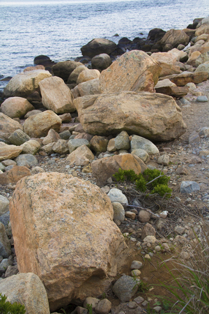 madison: Glacial boulders, rocks and gravel in curving line at waters edge, Hammonasset Beach, Madison, Connecticut. Stock Photo