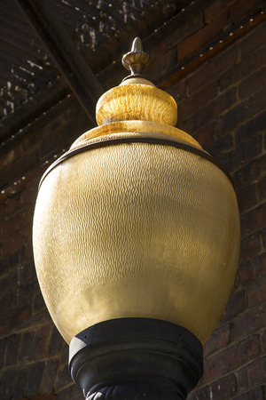 fixture: Vintage light fixture, with yellowing glass globe nearly filling the frame, on brick wall in alley, downtown Keene, New Hampshire.