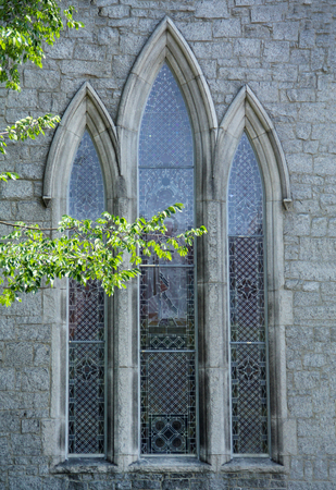 episcopal: Trio of vertical, pointed windows in gray stone facade of St. James Episcopal Church, downtown Keene, New Hampshire.