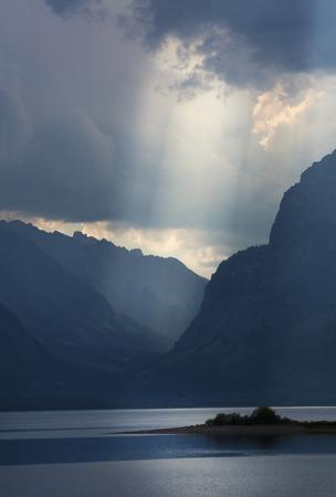 jackson: Dramatic dark clouds with beam of sun rays over Jackson Lake, Jackson Hole, Wyoming, vertical. Stock Photo