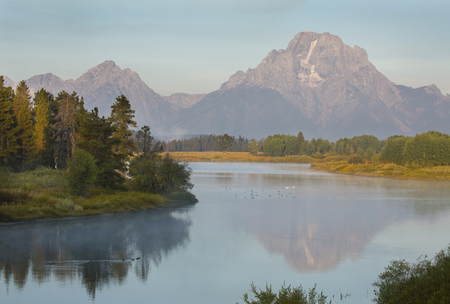oxbow: Red glow of sunrise on Mt. Moran, Grand Teton National Park, with reflection in still water of the Snake River at Oxbow Bend.