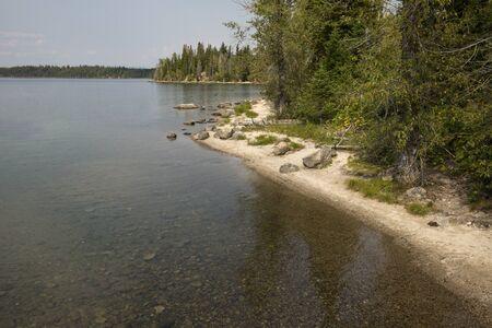 jackson: Curving, sandy shoreline along Jenny Lake, Jackson Hole, Wyoming, on a sunny summer day, horizontal.