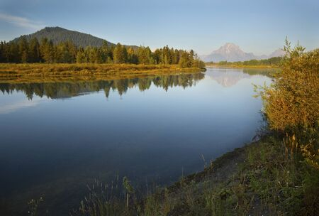 oxbow: Mirror surface of the Snake River at sunrise near Oxbow Bend, with the Teton Mountain Range in the background, Jackson Hole, Wyoming.