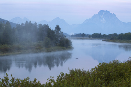 oxbow: The Snake River in the mist before dawn, with Teton mountains in the background and a red glow in the sky, from Oxbow Bend, Jackson Hole, Wyoming.