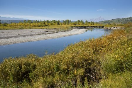 poplar  banks: Gravel banks along the Buffalo Fork River, with poplar trees and the Teton Mountains in the background,  Jackson Hole, Wyoming. Stock Photo