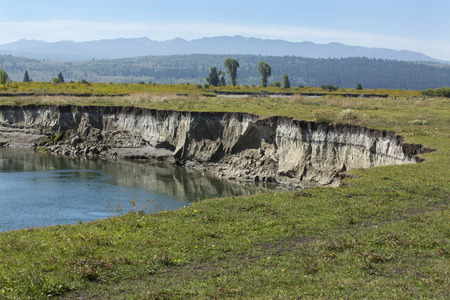 undercut: Winding course of the Buffalo Fork River near Moran, in northern Jackson Hole, Wyoming, with erosion into the pasture along the riverbank. Stock Photo