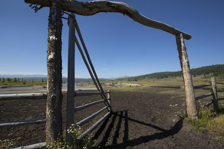 pasture fence: Gate in a horse pasture fence, with the Buffalo Fork River and the Grand Teton Mountains in the background, Moran, Wyoming.