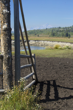 pasture fence: Gate in a horse pasture fence, with the Buffalo Fork River and the Grand Teton Mountains in the background, Moran, Wyoming, vertical image. Stock Photo