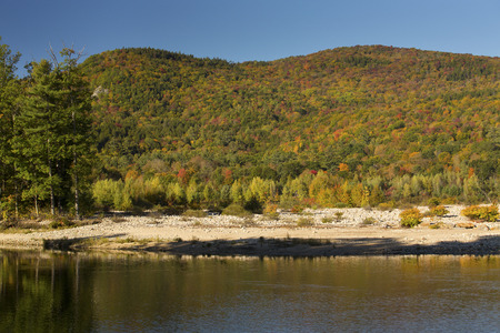 woodstock: Pemigewasset River in North Woodstock, New Hampshire, in the White Mountains National Forest, with mountain ridges and fall foliage. Stock Photo